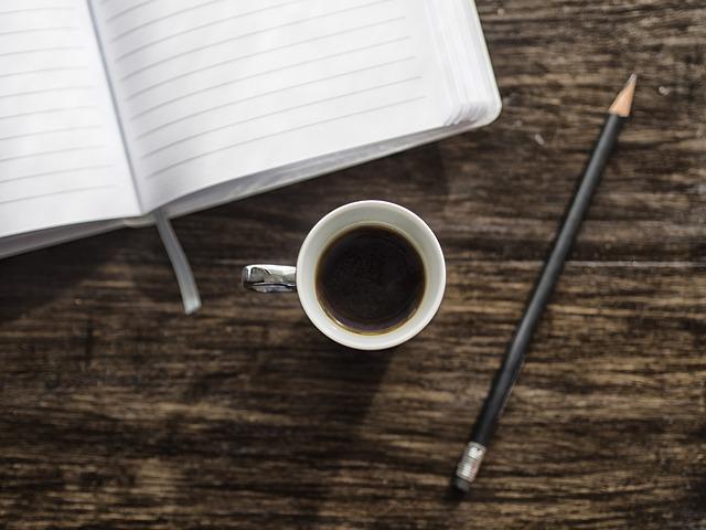 Eine Tasse Kaffee auf einem Holztisch, oben ein Notizbuch, rechts ein Bleistift