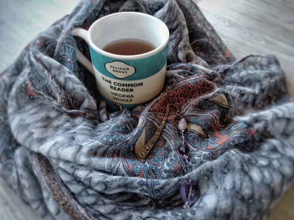Eine Tasse Tee in einen blauen Schal gehüllt.